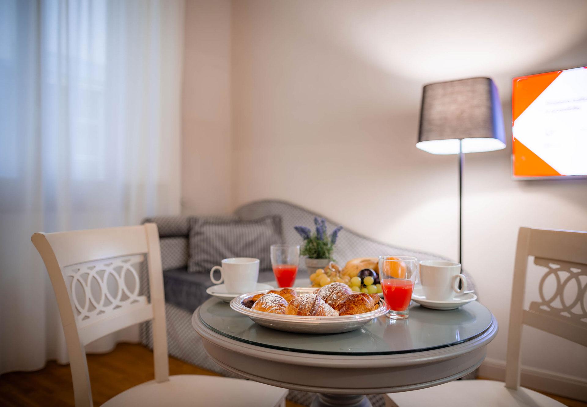 tavolino con colazione all'interno di una camera tripla dell'hotel del Corso in centro a Firenze